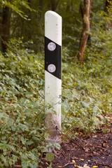 Deutscher Straßenbegrenzungspfeiler am Waldrand