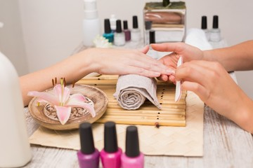 Nail technician giving customer a manicure