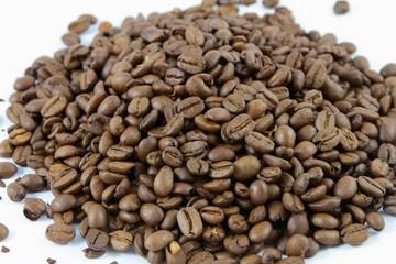 Detailaufnahme von einem Haufen Kaffeebohnen auf weißem Grund
