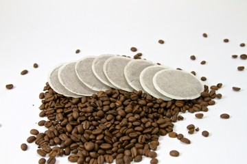 Kaffeepads mit verstreuten Kaffeebohnen