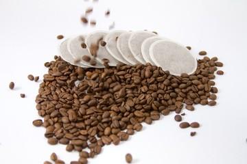 Kaffeepads mit fallenden Kaffeebohnen