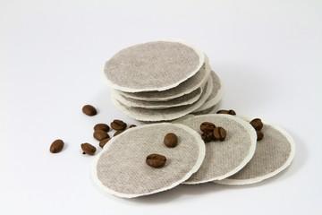 Neun Kaffeepads mit einzelnen Kaffeebohnen auf weißem Grund
