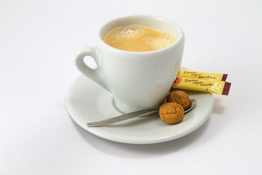 Kaffeetasse mit Zuckertütchen und Gebäck auf weißem Grund