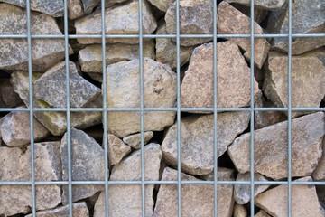 Detailaufnahme einer Gabionen-Mauer gefüllt mit Bruch-Kalkstein