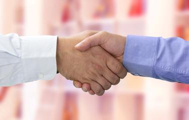 Hände beim Vertragsabschluss mit rotem Hintergrund