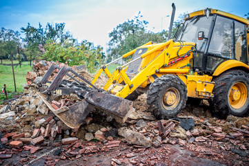 bulldozer working at demolition site, cleaning debris of bricks