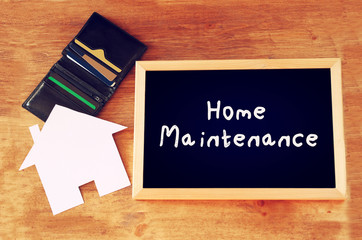 blackboard with the phrase home maintenance written on it over w