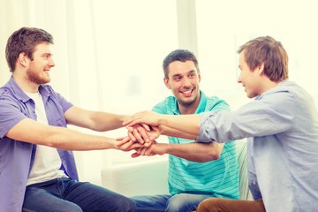 smiling male friends with hands together at home
