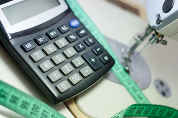 calculator at white sewing machine and green measuring tape