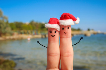 Finger art of a Happy couple  in Christmas hats resting on sea