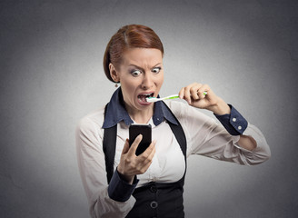shocked woman reading news on smartphone brushing teeth