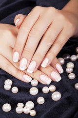 Fototapete - Beautiful woman's nails with french manicure and pearls.