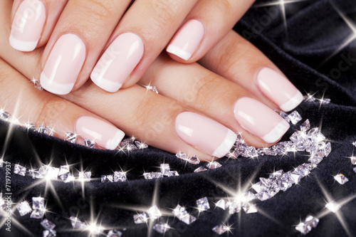 Wall mural Beautiful woman's nails with french manicure and diamonds.