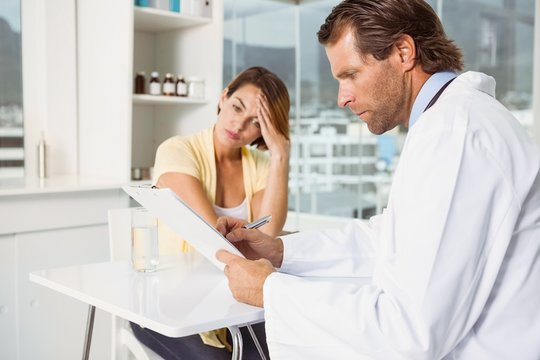 Doctor discussing reports with patient at desk medical
