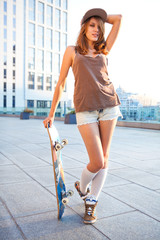 Beautiful sexy swag girl wearing baseball cap leans skateboard