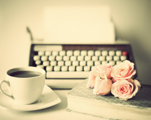Vintage typewriter and roses over book with coffee cup