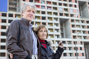 Senior couple standing with house keys against apartment