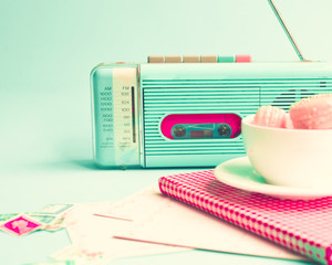 Pink macaroons in a tea cup and vintage radio