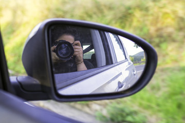 Photographer self portrait in a car mirror. Color image