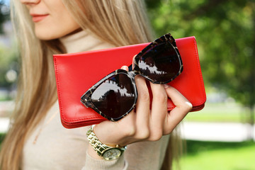 Wall Mural - fashion young woman holding red purse clutch in hand autumn