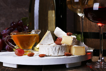 Supper consisting of Camembert cheese, honey, wine and grapes
