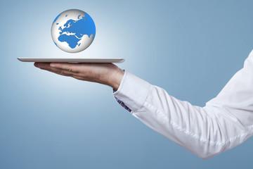 Hand hält Tablet darüber eine 3D Weltkugel