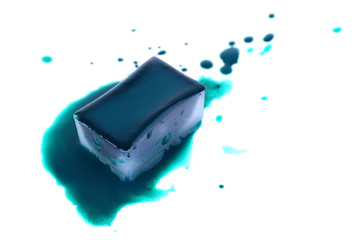 Watercolor paint cube and spilled paint isolated on white
