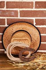 American West still life with old horseshoe, hat and cowboy