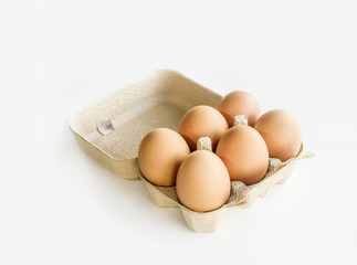 6 farm fresh chicken eggs in a tray over white.