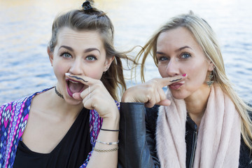 two women with a painted mustache