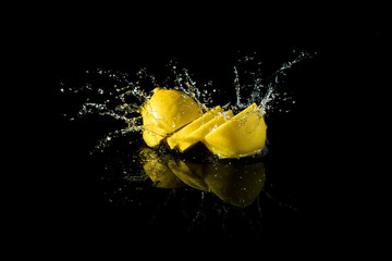 Sliced lemon splash on black background