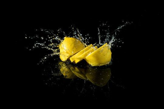 Sliced lemon splash on black background