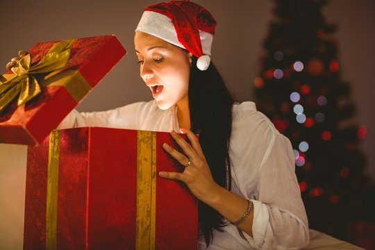 Festive brunette opening a glowing christmas gift