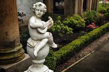 Statue of Cupid playing the guitar