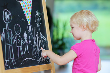 Funny toddler girl drawing family with chalk on black board