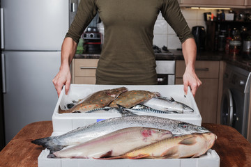 Woman with a box of fish in her kitchen