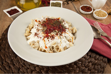 Turkish Manti manlama on plate with  tomatoes sauce, yogurt