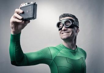 Superhero taking a selfie with a vintage camera