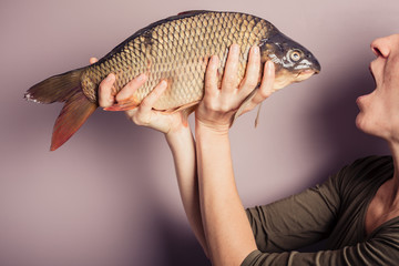 Silly young woman posing with a carp