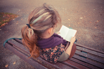 Young woman sitting on park bench with book