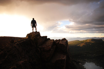 Silouette of Man on Top of Mountain at Sunset