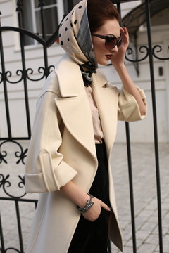 beautiful woman in elegant coat and silk scarf on head