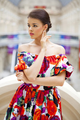 Beautiful woman in red flowers dress in the shop