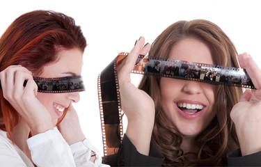 Zwei Frau haben Kopfkino und blicken durch Filmstreifen