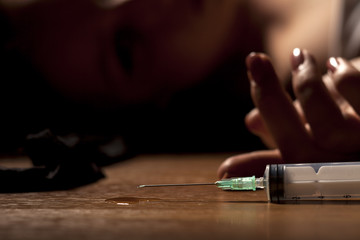 drugged woman lying on the floor with a syringe next to her