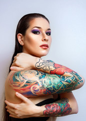 Beautiful girl with stylish make-up and tattooed arms,.