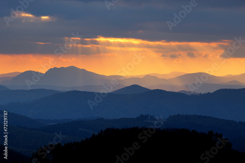 Wall mural Sunset over color mountain silhouette.