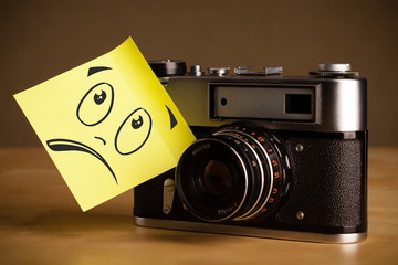 Post-it note with smiley face sticked on photo camera