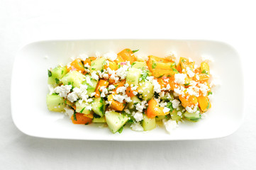 healthy tomato and cucmber salad served greek-style with feta ch