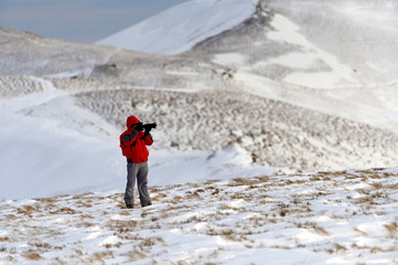 Photographer in winter mountain